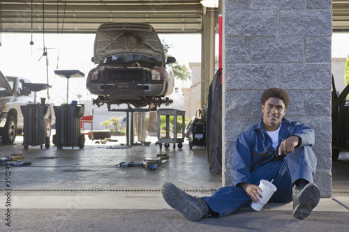 Mixed race mechanic taking a break in auto repair ship