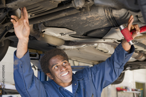 Mixed race mechanic working in auto repair shop