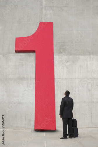 Hispanic businessman looking at large number 1
