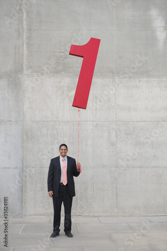 Hispanic businessman holding balloon shaped like number 1