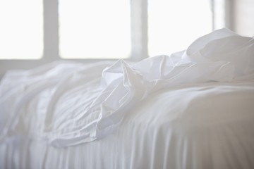 Close up of white sheets on bed