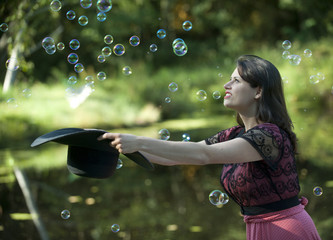 Caucasian woman trying to catch bubbles in hat