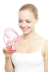 girl looking into a hand mirror on a white background