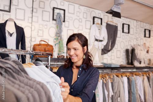 lächelnde frau kauft in einer boutique