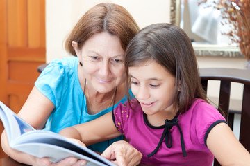 Grandmother and granddaughter reading a book at home.
