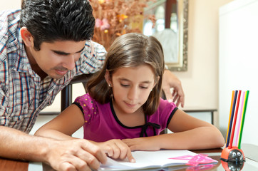 Latin father helping his daughter with homework
