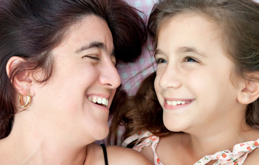 Hispanic mother and daughter laughing in their bed