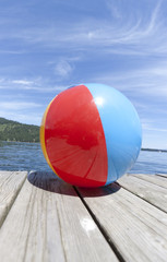 Colorful beachball on a dock in full summer sun