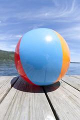 Colorful beachball on a dock in full summer sun
