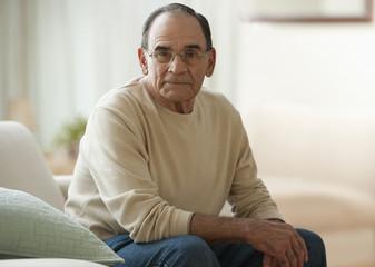 Senior Hispanic man sitting in living room