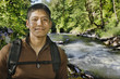 Mixed race man hiking near river