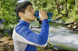 Mixed race man drinking water near river