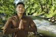 Mixed race man meditating near river
