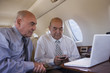 Hispanic businessmen working on private jet