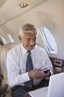 Hispanic businessman using cell phone on private jet