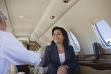 Business people shaking hands on private jet