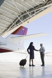 Hispanic business people meeting in airplane hangar