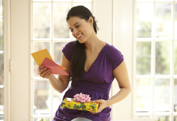 Hispanic woman holding gift and reading card