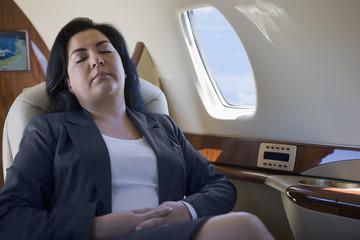 Hispanic businesswoman sleeping on private jet