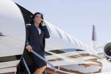 Hispanic businesswoman exiting private jet