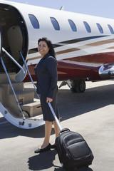 Hispanic businesswoman boarding private jet