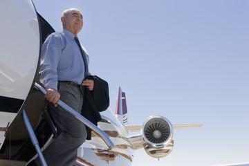 Hispanic businessman exiting private jet