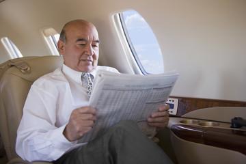 Hispanic businessman reading newspaper on private jet