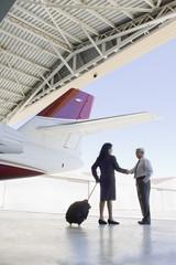 Hispanic business people meeting in airplane hangar