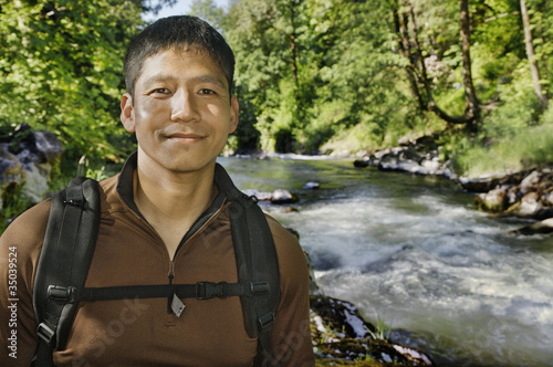 Mixed race man hiking near river