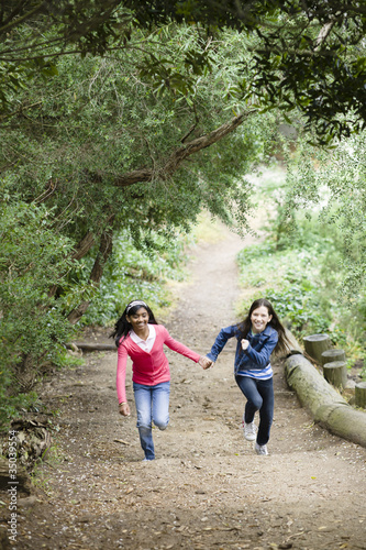 Girls holding hands and running on path