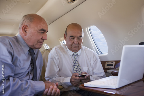 Hispanic businessmen working on private jet