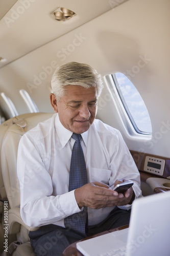 Hispanic businessman using cell phone on private jet