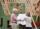 Caucasian couple looking at blueprints outside house under construction