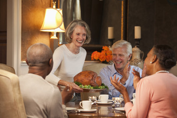 Smiling woman serving Thanksgiving turkey to clapping friends at dining room table