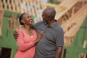 Smiling Black couple outside house under construction