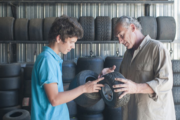 Hispanic grandfather and grandson looking at go-cart tires