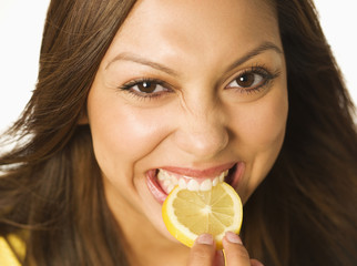 Close up of Hispanic woman biting lemon slice