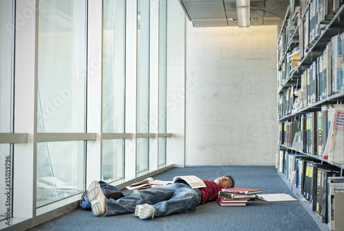 Books surrounding exhausted Hispanic student laying on library floor