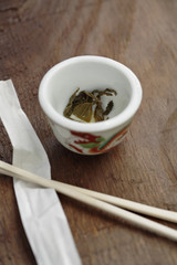 Close up of tea leaves in cup next to chopsticks