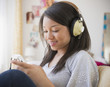 Smiling mixed race teenage girl listening to headphones
