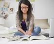 Mixed race teenage girl doing homework on bed