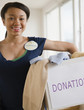 Smiling mixed race teenage girl wearing 'Volunteer' pin and holding box of donations