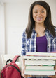 Smiling mixed race teenage girl holding stack of books