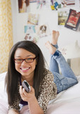 Mixed race teenage girl holding remote control and laying on bed