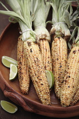 Roasted corn on the cob and limes in bowl