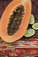 Close up of split papaya and limes