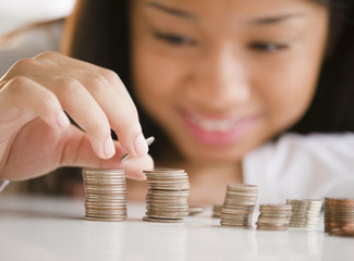Close up of mixed race teenage girl stacking coins