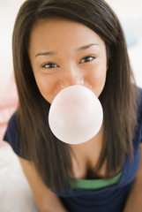 Close up of mixed race teenage girl blowing bubble with gum