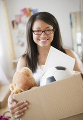 Smiling mixed race teenage girl holding box of belongings