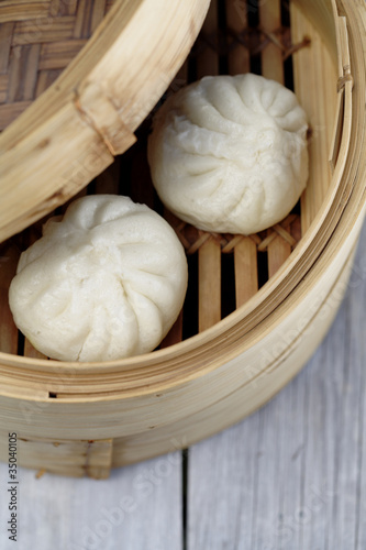 Close up of steamed dim sum pork buns in bamboo basket